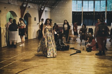 The same group of people as previously but now in a disorganised group. There are LARP weapons on the floor and one femme presenting person in a gown walking away from the others. photo credit Tom Garnet